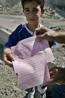 A Lebanese boy shows a leaflet distributed by Hezbollah supporters