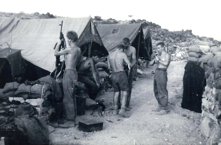 Richard Haselip cleaning his Bren Gun (far left)