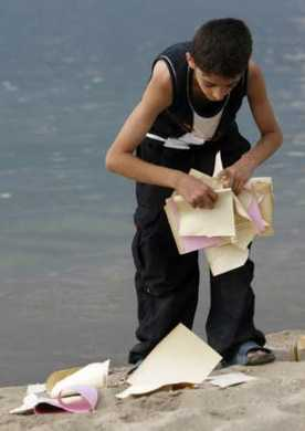A young Lebanese boy collects Israeli air-dropped leaflets in Beirut.