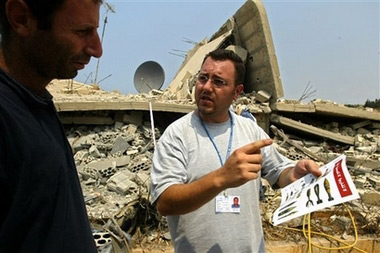 Elias Kayyal, an officer of the United Nations Mine Action Coordination Center holds a leaflet depicting unexploded ordinance in the village of Al Bayyadah, southern Lebanon