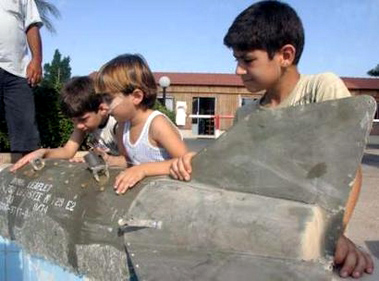 Lebanese children inspect a leaflet bomb that was dropped in Sidon, south Lebanon, July 24, 2006. REUTERS/Ali Hashisho