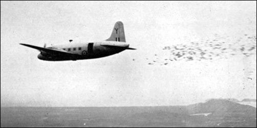 A Royal Air Force Valetta drops leaflets from 400 feet over the Malayan jungle.