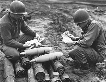U.S. soldiers examine Safe Conduct Passes as they are loaded into 105mm Propaganda Shells for artillery dissemination