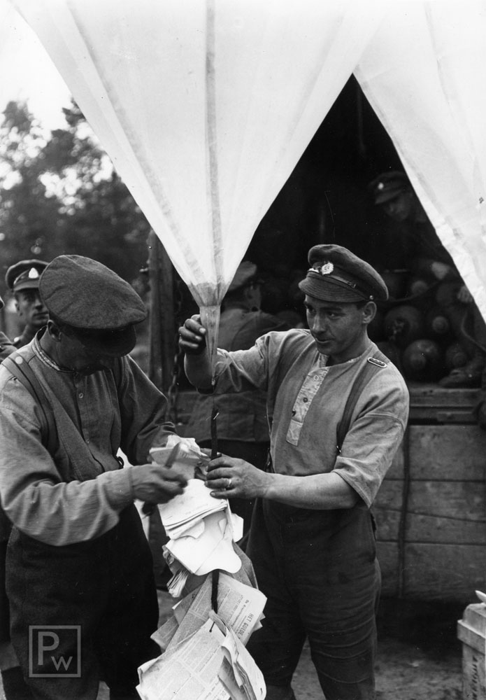WWI British balloon distribution of propaganda leaflets. Men of the Hampshire Regiment attaching leaflets to a balloon, near Bethune, France.