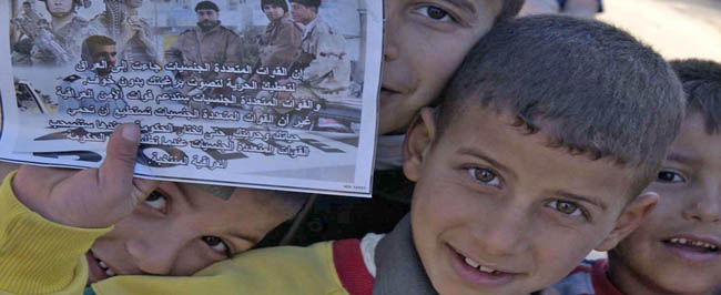 Young Iraqi boys hold a voting flyer.